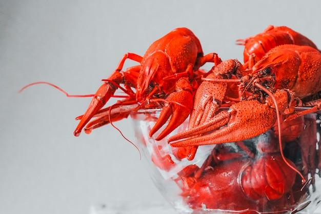 De délicieuses écrevisses chaudes avec une assiette sur fond rustique. délicieuses écrevisses bouillies rouges sur table, gros plan. conception de bannière