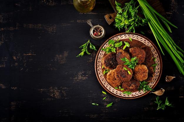 Délicieuses escalopes de viande juteuses sur une table sombre. cuisine russe. vue de dessus