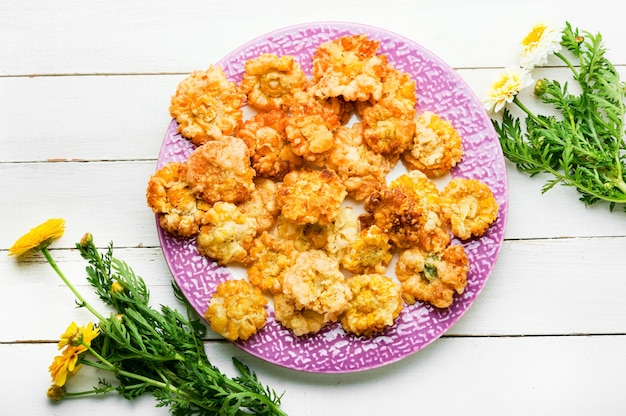 Délicieuses fleurs comestibles frites. fleurs de chrysanthème dans la pâte. nourriture végétalienne