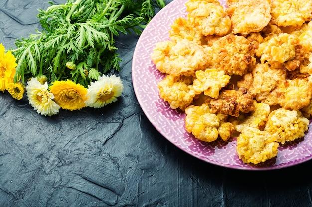 Délicieuses fleurs comestibles frites. fleurs de chrysanthème en pâte