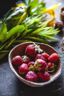 Délicieuses fraises aux fleurs jaunes sur un gris foncé dans une couronne vintage. nourriture saine