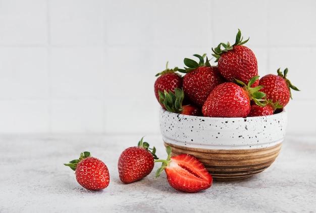 De délicieuses fraises mûres fraîches dans un bol blanc sur fond de pierre grise