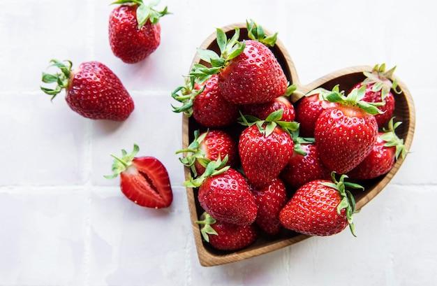 De délicieuses fraises mûres fraîches dans un bol en bois en forme de coeur sur fond de tuile rose