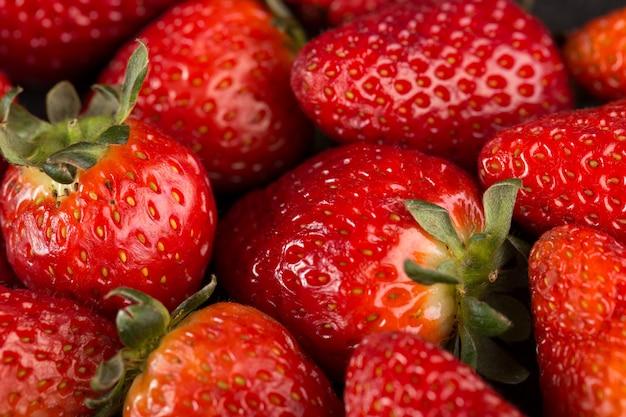 Délicieuses fraises rouges mûres avec des feuilles vertes sur un bureau sombre