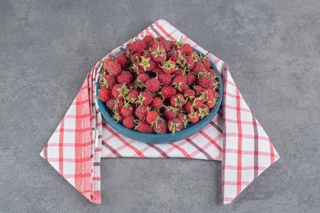 Délicieuses framboises rouges sur plaque bleue. photo de haute qualité