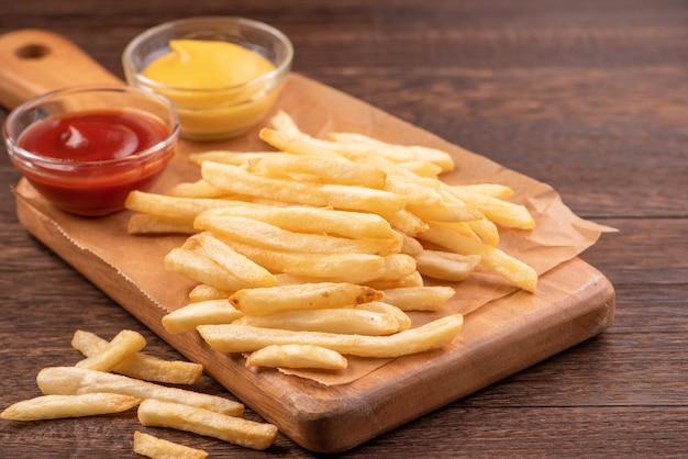 Délicieuses frites dorées sur une plaque à pâtisserie kraft et plateau de service à manger avec du ketchup et de la moutarde jaune, gros plan, style de vie.