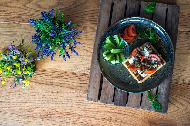 Délicieuses gaufres belges salées avec tomates séchées et olives kalamata sur plaque verte
