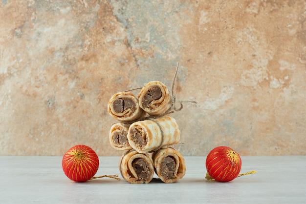 Délicieuses gaufres avec deux boules de noël rouges sur fond de marbre. photo de haute qualité