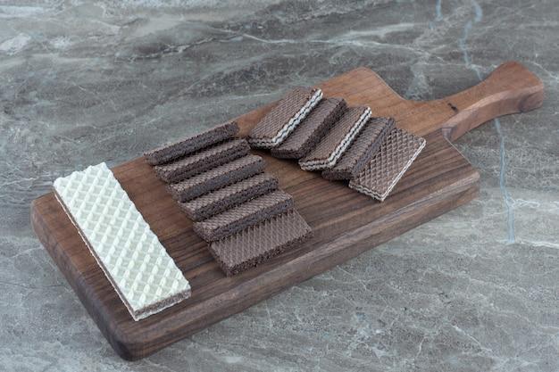 De délicieuses gaufrettes sucrées en planche à découper en bois.