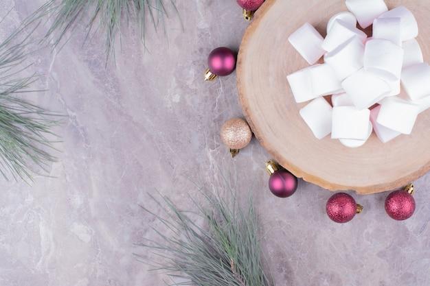 Délicieuses guimauves sur une planche de bois avec des boules de chêne autour