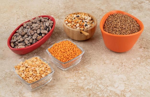 Délicieuses lentilles et haricots dans des assiettes sur une surface en marbre