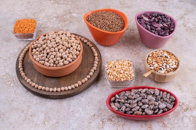 Délicieuses lentilles et haricots dans des assiettes sur une surface en marbre.