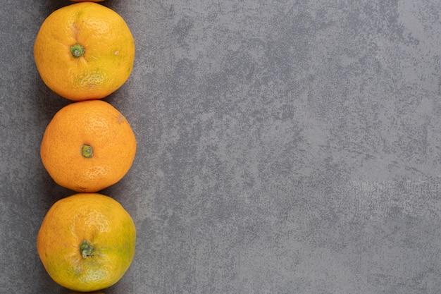 De délicieuses mandarines entières sur fond de marbre. photo de haute qualité