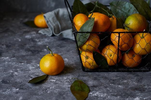 Délicieuses mandarines avec des feuilles dans un panier