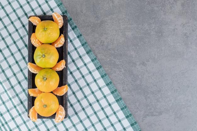De délicieuses mandarines et segments sur plaque noire. photo de haute qualité