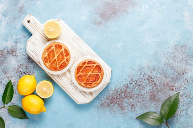 Délicieuses mini tartes au citron avec des citrons frais, vue de dessus