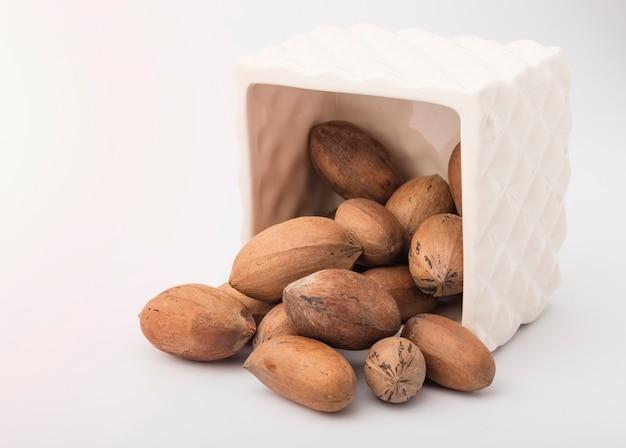 De délicieuses noix de pécan sont versées dans une tasse blanche sur fond blanc. espace de copie
