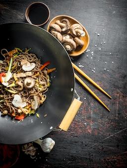 Délicieuses nouilles chinoises soba wok avec boeuf, champignons et légumes. sur rustique foncé