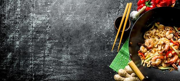 Délicieuses nouilles chinoises udon aux crevettes, sauce et légumes. sur table rustique sombre