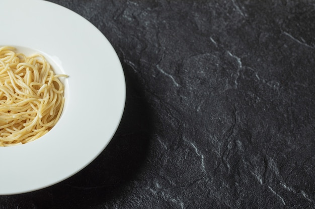 Délicieuses nouilles dans une assiette blanche sur fond noir.