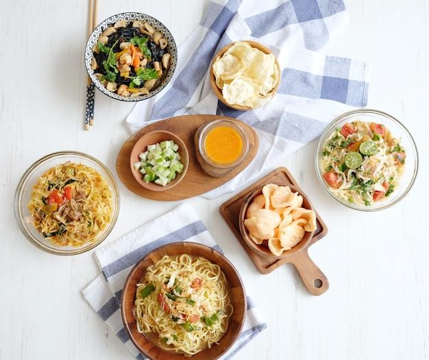 Délicieuses nouilles à la viande, craquelins tomates, sauce chili sur la table blanche
