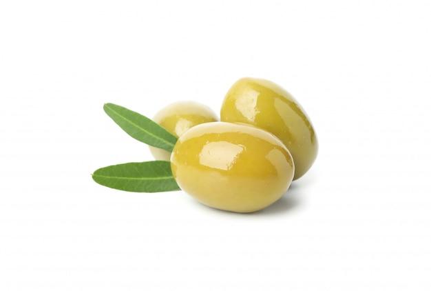 Délicieuses olives vertes et feuilles isolées sur blanc, gros plan