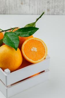 Délicieuses oranges avec branche dans une boîte en bois