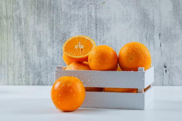 Délicieuses oranges avec des gouttes dans une boîte en bois blanche sur un mur gris blanc et grungy, vue latérale.