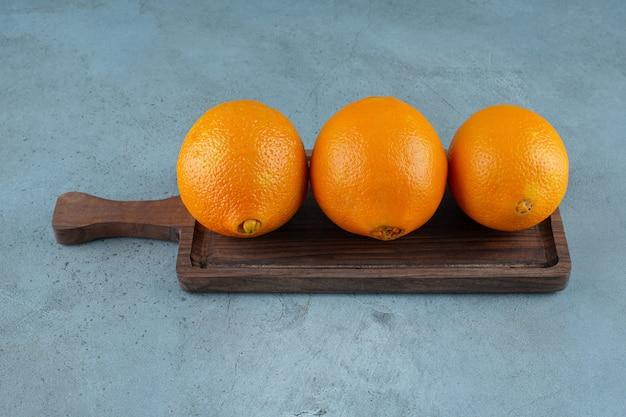 Délicieuses oranges sur une planche, sur fond de marbre. photo de haute qualité