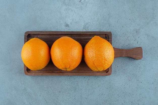 Délicieuses oranges sur une planche, sur fond de marbre.
