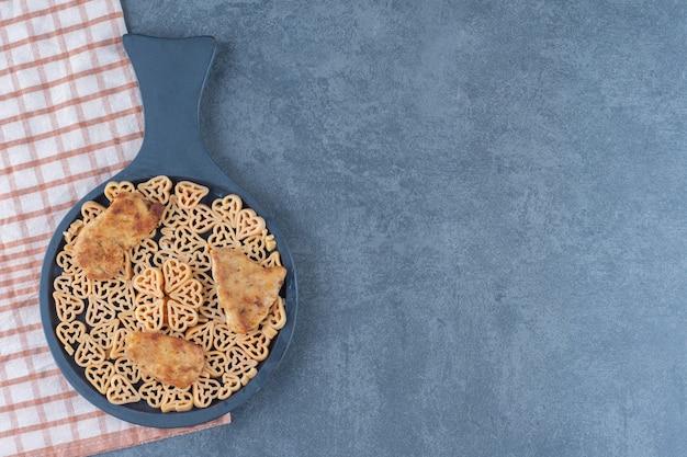 Délicieuses pâtes aux pépites sur tableau noir.