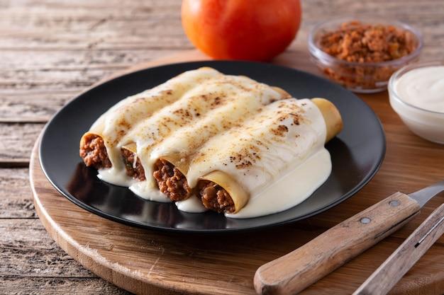 Délicieuses pâtes cannelloni de viande sur table en bois
