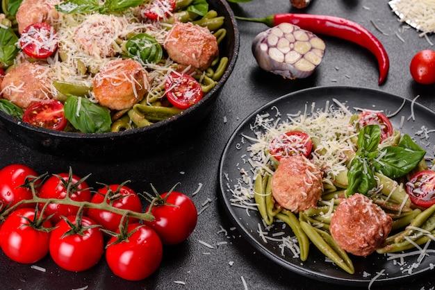 Délicieuses pâtes fraîches avec boulettes de viande, sauce, tomates cerises et basilic