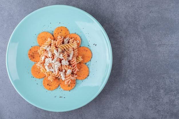 Délicieuses pâtes fusilli et carottes sur plaque bleue.