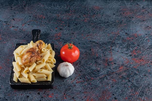 Délicieuses pâtes penne et cuisse de poulet sur une planche à découper noire.