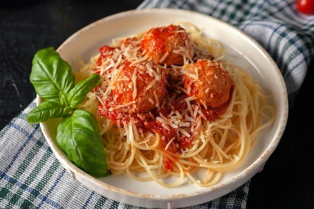 Délicieuses pâtes spaghetti aux boulettes de viande, parmesan et sauce tomate sur une assiette sur un torchon de cuisine