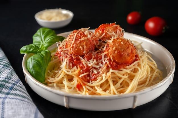 Délicieuses pâtes spaghetti aux boulettes de viande, parmesan et sauce tomate sur une assiette
