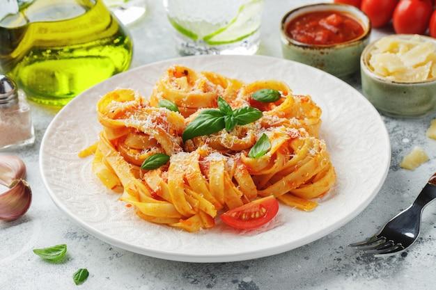Délicieuses pâtes tagliatelles italiennes classiques appétissantes avec sauce tomate, fromage parmesan et basilic sur assiette sur table lumineuse. vue de dessus, horizontale.