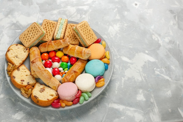 Délicieuses pâtisseries avec macarons et bonbons sur tableau blanc