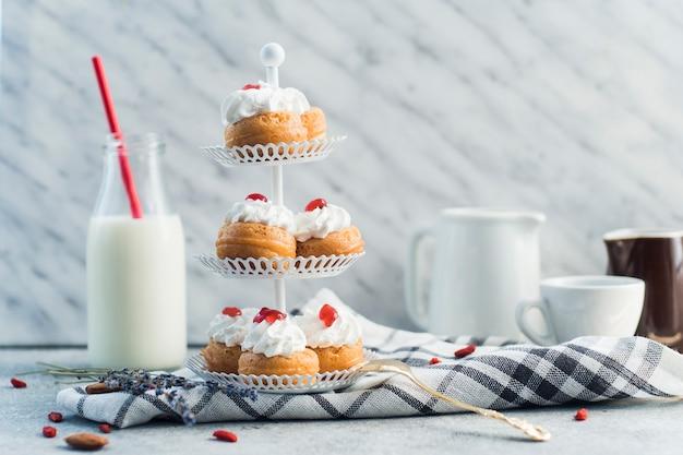 Délicieuses pâtisseries placées sur un présentoir à gâteau près d'une bouteille de lait et de la nourriture pour noix sur une surface en béton