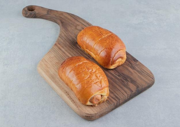 De délicieuses pâtisseries avec des saucisses sur planche de bois.