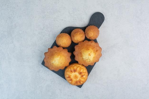 Délicieuses pâtisseries sucrées sur tableau noir