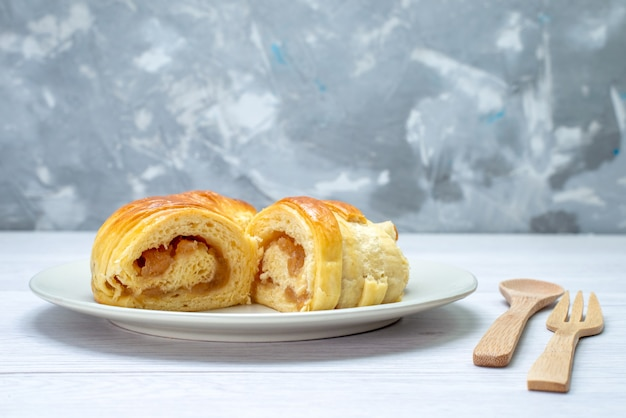 Délicieuses pâtisseries en tranches à l'intérieur de la plaque avec garniture avec cuillère fourchette en bois sur blanc, biscuit pâtisserie biscuit sucre sucré