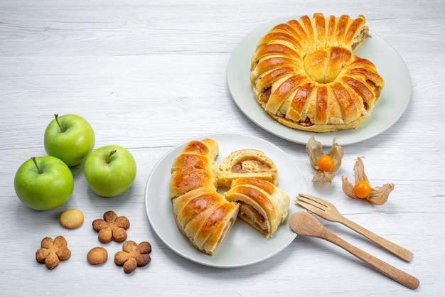 Délicieuses pâtisseries en tranches à l'intérieur de la plaque avec remplissage avec pommes vertes et cookies sur un bureau blanc, biscuit pâtisserie biscuit sucre
