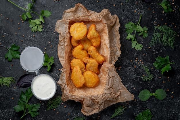 De délicieuses pépites de poulet croustillantes sur un fond de pierre sombre avec une sauce crémeuse. restauration rapide. option saine de restauration rapide.
