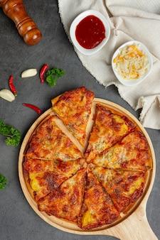 Délicieuses pizzas hawaïennes et ingrédients de cuisine.