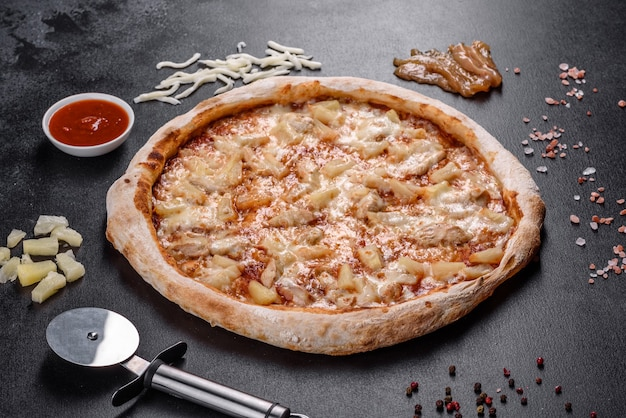 De délicieuses pizzas italiennes fraîches avec du poulet, des tomates et de l'ananas sur un fond de béton foncé. cuisine italienne