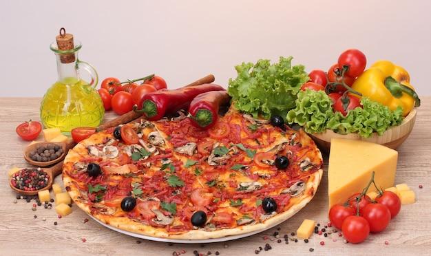 Délicieuses pizzas et légumes sur table en bois