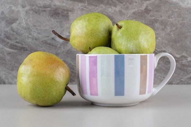 Délicieuses poires dans et à côté d'une grande tasse sur marbre