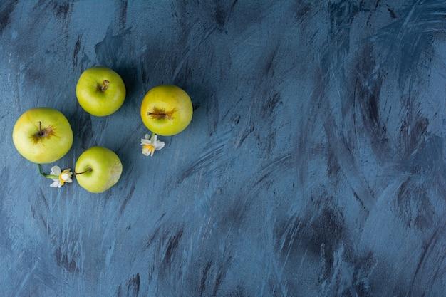 De délicieuses pommes fraîches vertes placées sur une table bleue.